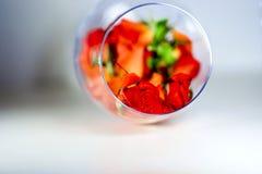 Стеклянная ваза заполненная с лепестками красной розы aromatherapy принципиальная схема Стоковые Изображения RF