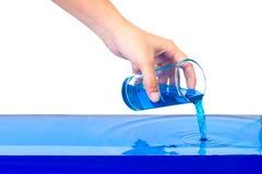стеклянная вода удерживания руки Лить голубая жидкость на изолированной белой предпосылке Стоковое Изображение RF