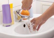 стеклянная вода удерживания руки Стоковое Изображение