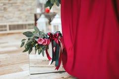Стеклянная коробка с розовыми розами на верхней части стоит под красной тканью Стоковая Фотография