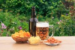 Стеклянная кружка пива и бутылки пива на деревянном столе с картошкой Стоковое Фото