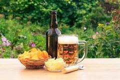 Стеклянная кружка пива и бутылки пива на деревянном столе с картошкой Стоковые Изображения
