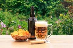 Стеклянная кружка пива и бутылки пива на деревянном столе с картошкой Стоковое фото RF