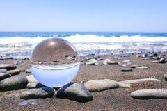 Стеклянная сфера на камнях на пляже в Мадейре Стоковая Фотография