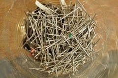 Стеклянная тара с кучей серебряных штырей используемых в швейной промышленности одежды Стоковая Фотография