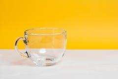 Стеклянная чашка на белой таблице Желтая предпосылка Стоковая Фотография