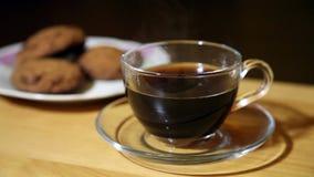 Стеклянная чашка с кофе и печеньями на плите сток-видео