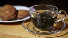 Стеклянная чашка с чаем и печеньями на плите акции видеоматериалы