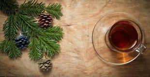 Стеклянная чашка чаю на старой деревенской таблице с ветвью сосны Новый Yea стоковая фотография
