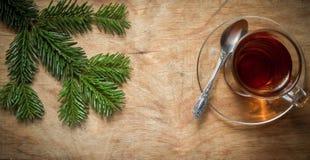 Стеклянная чашка чаю на старой деревенской таблице с ветвью сосны Новый Yea стоковые изображения rf