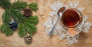 Стеклянная чашка чаю на старой деревенской таблице с ветвью сосны Новый Yea стоковые фото