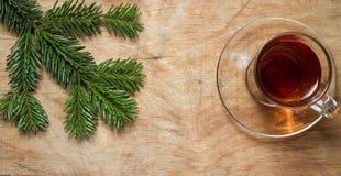 Стеклянная чашка чаю на старой деревенской таблице с ветвью сосны Новый Yea стоковое фото