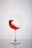 Стеклянное красное вино брызгая на белой предпосылке Стоковые Изображения