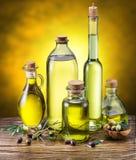 Стеклянные бутылки оливкового масла и немногих ягод на деревянном столе Стоковые Фото
