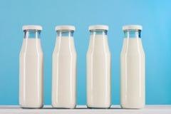 Стеклянные бутылки с молоком на столешнице на голубой предпосылке Стоковая Фотография