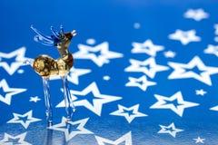 Стеклянные олени на голубой предпосылке с звездами стоковая фотография