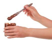 Стеклянные сливк и нож шоколада в изолированных женщинах рук Стоковые Изображения RF
