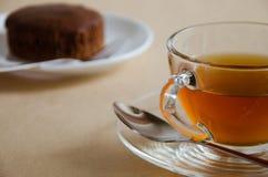 Стеклянные чашка чаю и шоколадный торт Стоковые Фотографии RF