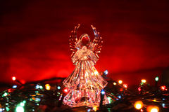 Стеклянный ангел с гирляндой на красной предпосылке Стоковая Фотография RF