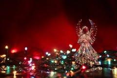Стеклянный ангел с гирляндой на красной предпосылке Стоковые Фотографии RF