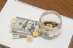 Стеклянный вполне монеток на египетских & американских банкнотах с Notebo Стоковая Фотография RF