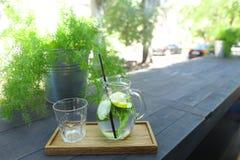 Стеклянный графинчик и граненная стеклом чашка стоят на планке на таблице внутри Стоковые Изображения RF