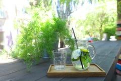 Стеклянный графинчик и граненная стеклом чашка стоят на планке на таблице внутри Стоковые Фотографии RF