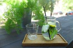 Стеклянный графинчик и граненная стеклом чашка стоят на планке на таблице внутри Стоковое Изображение RF