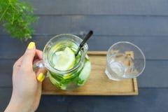 Стеклянный графинчик который держится в руке и стекле гранил стойку чашки Стоковая Фотография RF