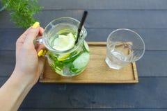 Стеклянный графинчик который держится в руке и стекле гранил стойку чашки Стоковая Фотография