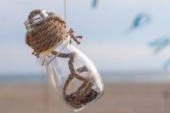 Стеклянный опарник красивых раковин на предпосылке моря Стоковые Фото