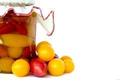 Стеклянный опарник при законсервированные изолированные томаты и свежие томаты Стоковые Изображения RF
