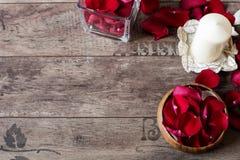 Стеклянный смычок вазы и древесины заполнил с лепестками красного цвета и белой розы, белой ароматичной ванильной свечой Деревянн Стоковое Фото