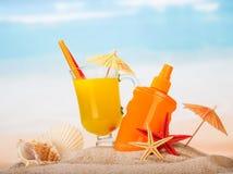 Стеклянный сок, солнцезащитный крем, зонтики, морские звёзды, раковины в песке против моря Стоковые Изображения