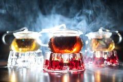 3 стеклянных чайника с подогревателями свечи и освещенным контржурным светом дымом дальше Стоковое Изображение
