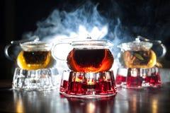 3 стеклянных чайника с подогревателями свечи и освещенным контржурным светом дымом дальше Стоковая Фотография