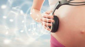 Стельность и нот принципиальной схемы. живот беременной женщины и headpho Стоковые Фото