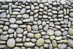 Стена внешнего камешка каменная с засорителем и мох растут на ем стена текстуры кирпича предпосылки старая Стоковая Фотография RF
