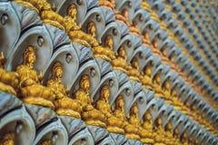 Стена в виске заполнена с buddhas Концепция буддизма вероисповедания Текстура, буддизм предпосылки стоковая фотография