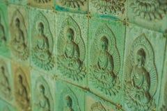 Стена в виске заполнена с buddhas Концепция буддизма вероисповедания Текстура, буддизм предпосылки стоковые фотографии rf