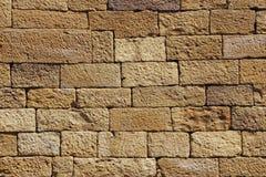 Стена желтого песка каменная для предпосылки или текстуры Стоковое Изображение