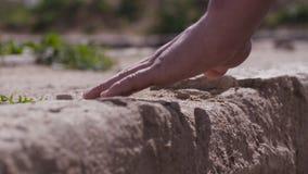Стена касания руки каменная Рука укомплектовывает личным составом касания каменная стена Укомплектуйте личным составом сильное же Стоковые Изображения RF