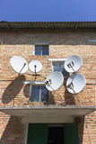 Стена дома красного кирпича с антеннами плиты спутниковой антенна-тарелки стоковое изображение rf