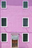 Стена покрашенная пинком с несколькими окон Стоковое фото RF