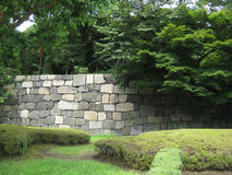 Стена положенная рукой каменная с деревьями и лужайкой Стоковое Изображение RF
