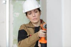Стена работника женщины сверля Стоковые Фотографии RF