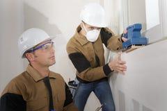 Стена работника полируя с боссом помощи Стоковые Изображения