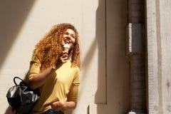 Стена счастливой молодой женщины готовя есть мороженое стоковые фотографии rf