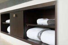 Свернутые белые полотенца на полке в ванной комнате гостиницы. Стоковое Изображение RF