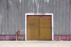 Стена фабрики металлического листа с красной входной дверью в промышленном парке Красная дверь здания фабрики Стоковое Изображение RF